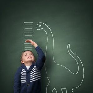 photo of boy and dinosaur on chalkboard